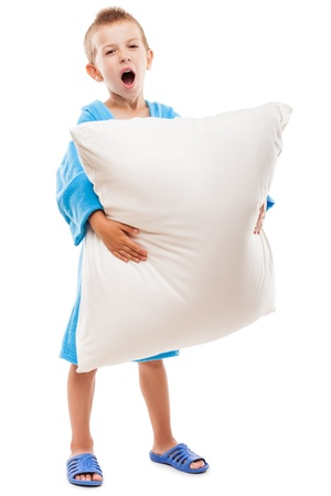 Little tired yawning child boy hand holding pillow going to sleep white isolated