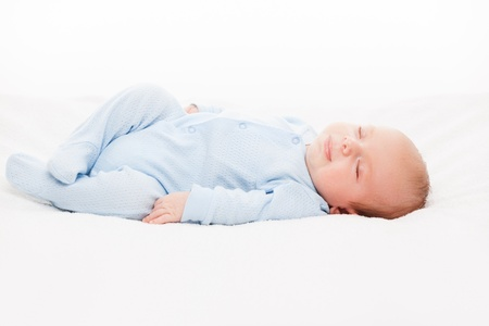 sleeping face: Little cute smiling newborn baby child sleeping bed white isolated Stock Photo