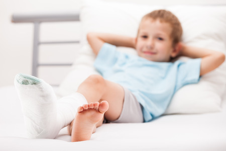 damaged: Human healthcare and medicine concept - little child boy with plaster bandage on leg heel fracture or broken foot bone