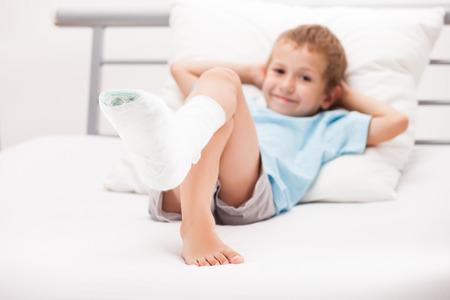 broken foot: Human healthcare and medicine concept - little child boy with plaster bandage on leg heel fracture or broken foot bone