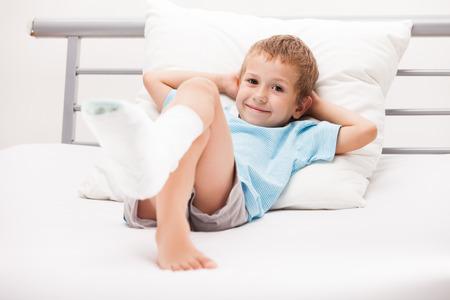 人間の薬と健康管理コンセプト - 石膏包帯足のかかとの骨折や骨折した足の骨を持つ小さな子供少年 写真素材