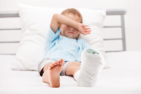 Menschliche Gesundheit und Medizin Konzept - kleines Kind Junge mit Gipsverband am Bein Ferse Fraktur oder gebrochenen Fußknochen