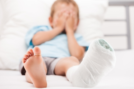 Human healthcare and medicine concept - little child boy with plaster bandage on leg heel fracture or broken foot bone photo