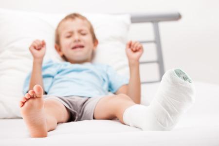 Menschliche Gesundheit und Medizin Konzept - kleines Kind Junge mit Gipsverband am Bein Fersenfraktur oder gebrochenen Fuß Knochen