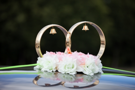 Just married gold rings and rose flowers decoration on wedding limousine car photo