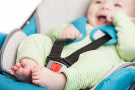 Little smiling baby child fastened with security belt in safety car seat