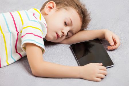 Little tired sleeping child boy hand holding digital tablet computer photo