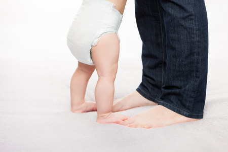 toddler walking: Walking toddler concept - little baby child boy making first step holding mother