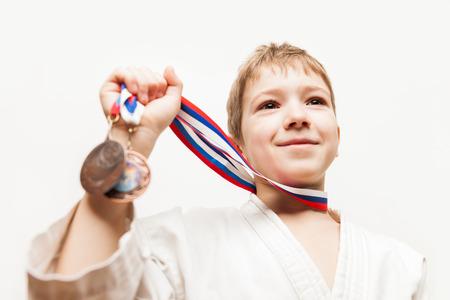 Martial art sport success and win concept - smiling karate champion child boy hand holding first place victory gold medal award Stock Photo