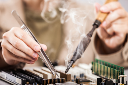 transistor: Manual worker human hand holding soldering iron tool repairing computer electronics circuit board