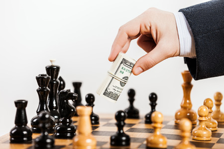 unfair: Business man hand holding dollar currency unfair playing chess game
