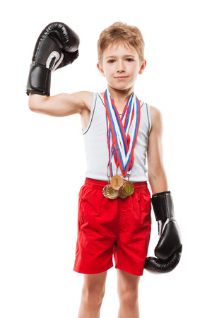 Martial art sport success and win concept - smiling boxing champion child boy holding first place victory gold medal award photo