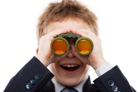 Little smiling child boy in business suit hand holding binoculars lens looking for direction white isolated photo
