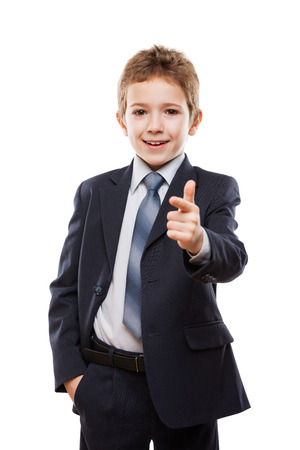 Gut aussehend lächelnd Kind Junge im Anzug Zeigefinger Richtung Weg oder Kampagne Rühren Wahl weiß isoliert
