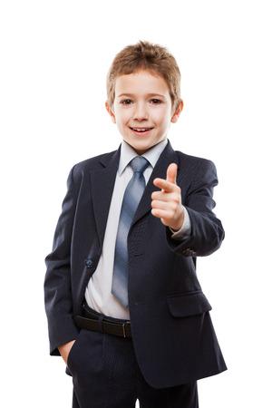 ni�os en la escuela: Muchacho hermoso ni�o sonriente en traje de negocios dedo �ndice se�alando la direcci�n camino o una campa�a de agitaci�n elecci�n blanco aislado