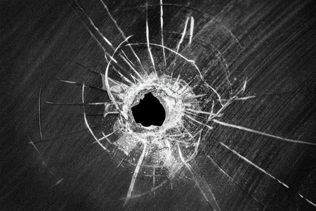 Bullet shot cracked hole on car windshield or accident damaged broken house window glass