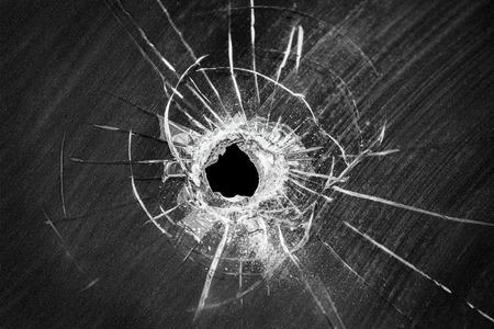 cristal roto: Disparo de bala agujero agrietada en el parabrisas del coche o accidente dañado roto el vidrio de ventana casa