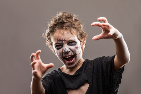 face zombie: Halloween or horror concept - screaming walking dead zombie child boy reaching hand