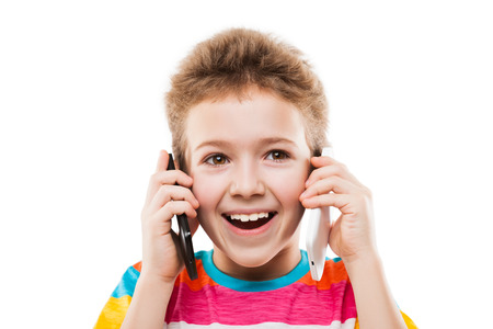 Beauty smiling child boy hand holding two mobile phones or talking pair of smartphones white isolated photo