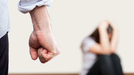Family violence and aggression concept - furious angry man raised punishment fist over scared or terrified woman sitting at wall corner