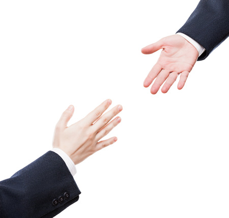 reach: Business support and assistance concept - businessman giving helping hand to team partner white isolated