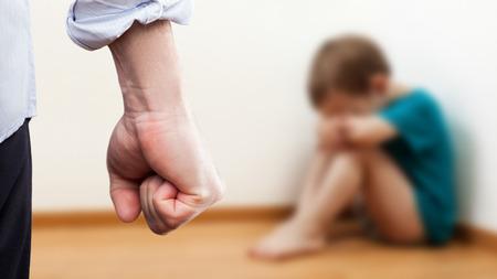 enfants chinois: La violence familiale et le concept de l'agression - furieuse colère homme élevé punition poing plus effrayé ou terrifié enfant garçon assis à angle de mur
