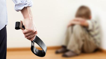 Familie Gewalt und Aggression Konzept - wütend wütenden Mann hob Strafe Hand Ledergürtel über Angst oder Angst Kind Junge sitzt am Wandecke