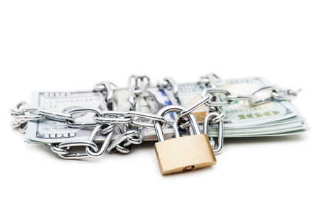 Business safety and finance protection concept - metal chain link with locked padlock on dollar currency money white isolated photo