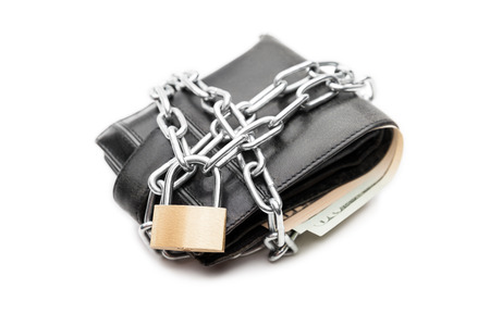 Business safety and finance protection concept - metal chain link with locked padlock on leather wallet full of dollar currency money white isolated photo