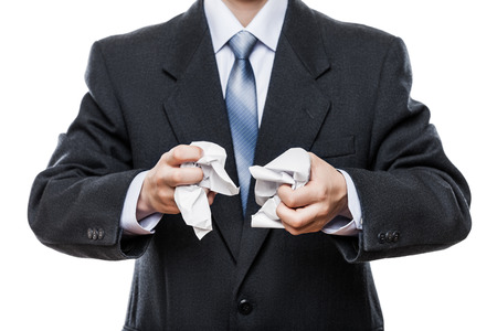 Business problems and failure at work concept - angry businessman in black suit hand holding crumpled torn paper document white isolated photo