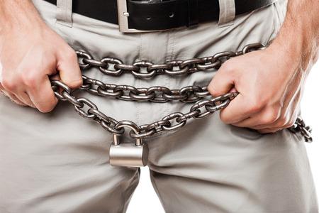 sexo: Cuestiones sexuales y prohibidos sexo concepto - hombre manos sosteniendo un candado cerrado de metal cintur�n de castidad de la cadena sobre los pantalones o jeans con cremallera