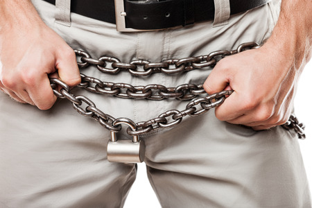 Sexual issues and forbidden sex concept - man hands holding padlock locked metal chain chastity belt over pants or jeans zip fly