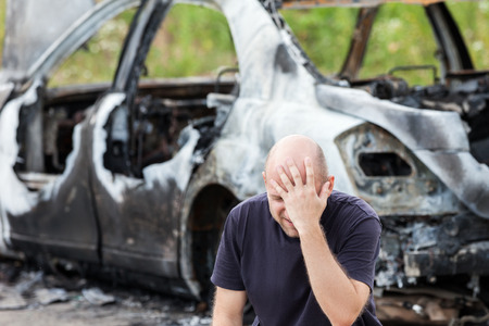 Crying upset caucasian man at road wreck accident or arson fire burnt wheel car vehicle junk photo