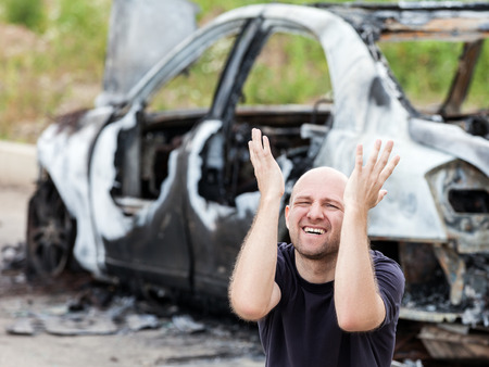 quemado: Crying hombre caucásico molesto por carretera accidente accidente o incendio provocado rueda quemada vehículo chatarra