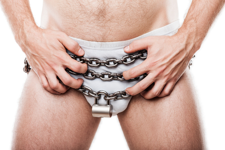 Sexual issues and forbidden sex concept - naked man hand holding padlock locked metal chain chastity belt over pants underwear photo