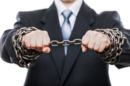 Business problems and failure at work concept - businessman struggles metal chain knot tied hands white isolated photo