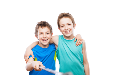Two handsome smiling child boy brothers hand holding mobile phone or smartphone selfie stick taking portrait photo white isolated photo