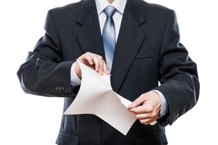 Business problems and failure at work concept - angry businessman in black suit hand tearing paper document white isolated photo