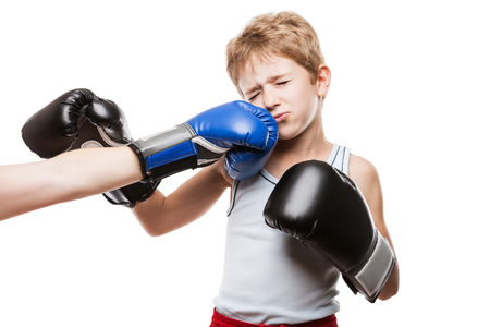 Martial art sport fail and lose concept - handsome boxer child boy in boxing gloves got punched photo