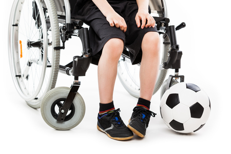 Invalid or disabled child boy sitting on wheelchair hand holding soccer sport ball white isolated photo