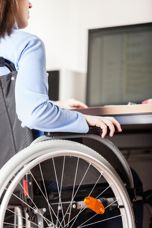 Invalid or disabled young business woman person sitting wheelchair working office desk computer Banque d'images