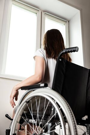 Invalid or disabled young woman person sitting wheelchair indoor looking window daylight bright sky Stockfoto