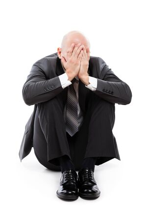 Business problems and failure at work concept - unhappy crying tired or stressed businessman sitting in depression hand hiding face white isolated
