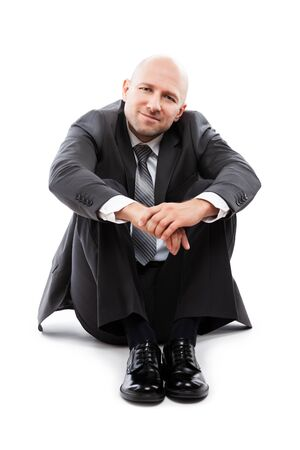 Business success concept - handsome happy smiling businessman in black suit sitting down floor white isolated