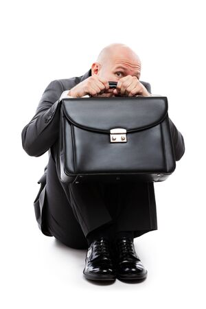 Business problems and failure at work concept - unhappy scared or terrified businessman in depression with fear and stress face expression hand holding briefcase sitting down floor white isolated Imagens