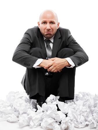 Business problems and failure at work concept - unhappy tired or stressed businessman in depression sitting down floor on crumpled torn paper document heap white isolated