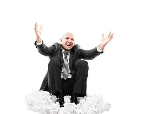 Problèmes commerciaux et concept d'échec au travail - cris ou cris d'homme d'affaires fatigué et stressé gesticulant les mains levées assis sur le sol sur un tas de document papier déchiré et froissé isolé blanc