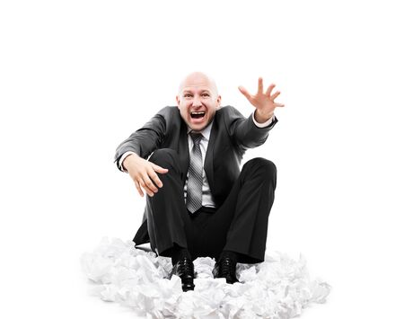 Business problems and failure at work concept - loud shouting or screaming tired stressed businessman gesturing raised hand for help sitting floor on crumpled torn paper document heap white isolated