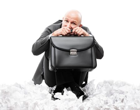 Business problems and failure at work concept - unhappy scared or terrified businessman in depression hand holding briefcase sitting down floor on crumpled torn paper document heap white isolated Stockfoto