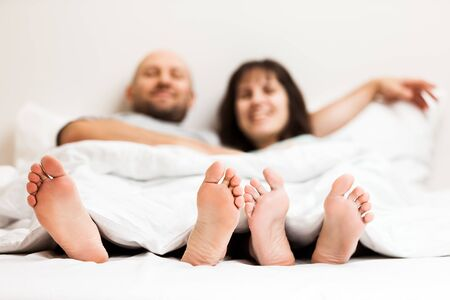 Love, dating, romantic mood, happy people and bedtime concept - attractive caucasian couple in relationship lying and hugging on bed in bedroom Stockfoto